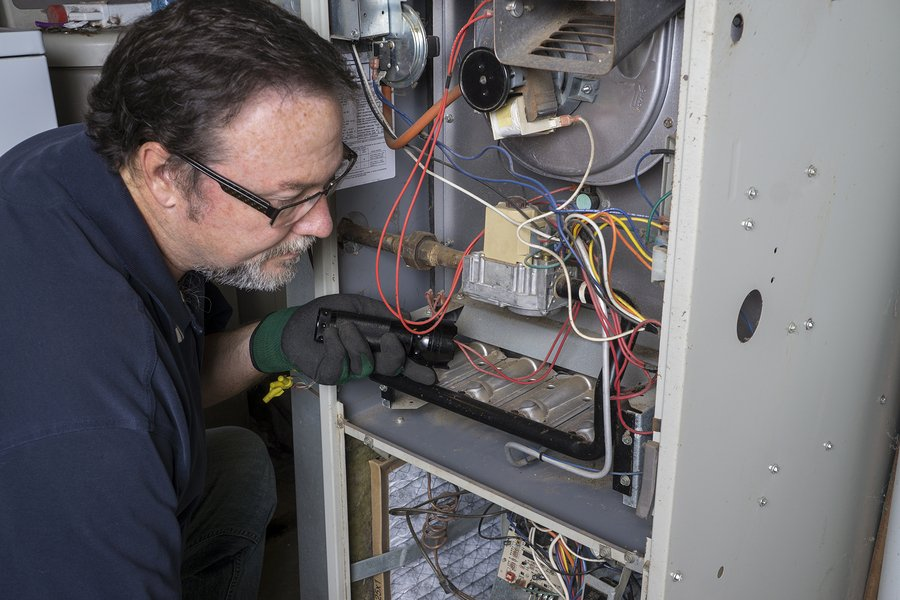 HVAC contractor repairing a furnace